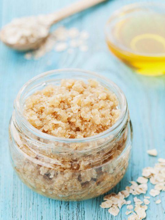 honey sugar scrub in a mason jar with oil in the background
