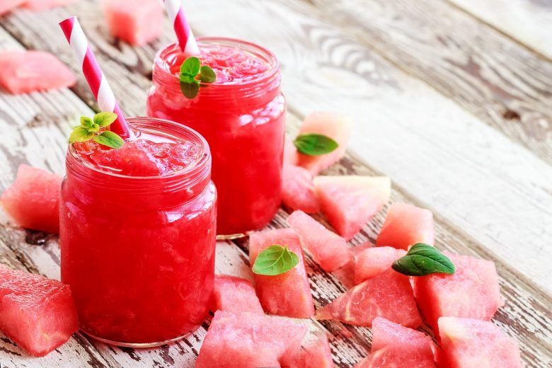 Cold fresh watermelon juice in glass bottles with mint on white wooden background