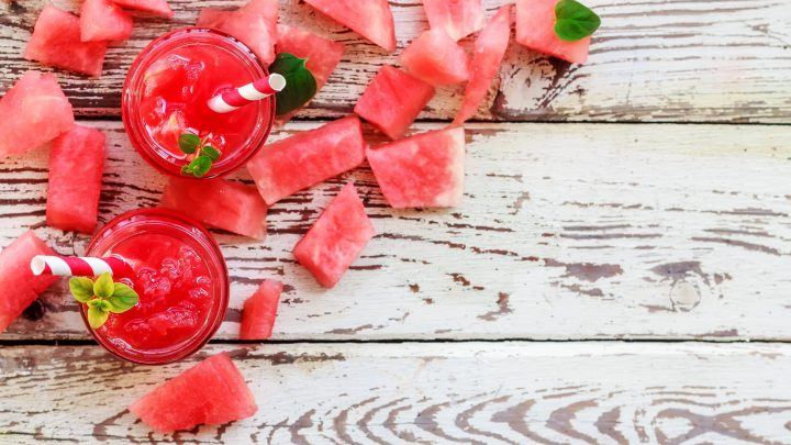 Healthy fresh watermelon juice in glass bottles with mint on white wooden background. Top view