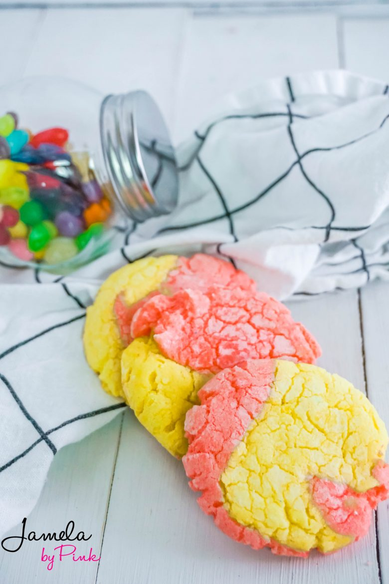 Lemon crinkle cookies with strawberry on a white towel with black lines and a jar of jelly beans in the distance