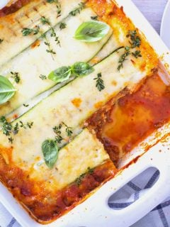 Top View Of Zucchini Lasagna In A White Dish with blue and white striped towel