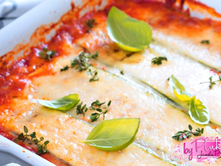 Top Close up view Zucchini Lasagna In A White Dish with blue and white striped towel