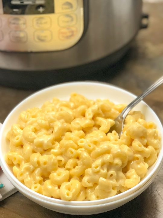 top view of 2 white bowls nested into each other with instant pot mac anc cheese in the bowl with a fork sticking out and an instant pot in the background.
