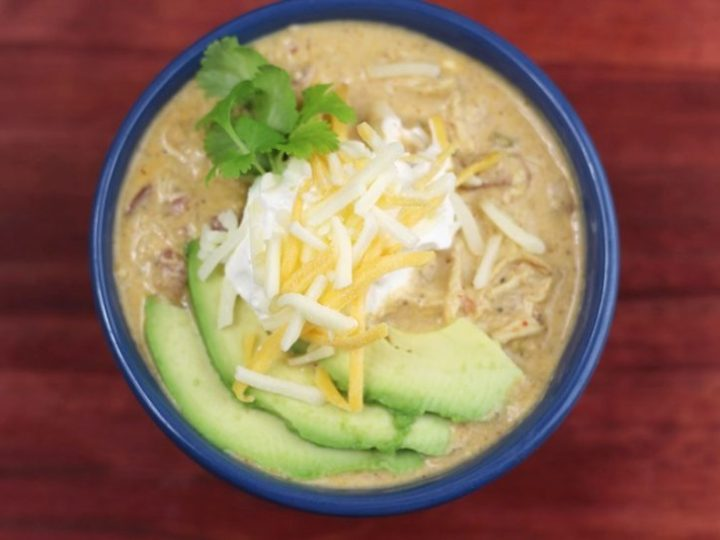 blue bowl on a red and white kitchen towel with white chicken chili instant pottopped with avocado, cheese, sour cream and cilantro