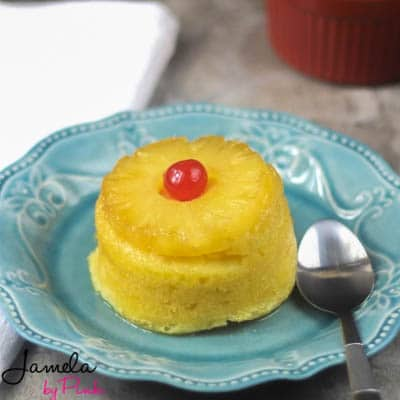side view of a mini pineapple upside down cake on a teal plate
