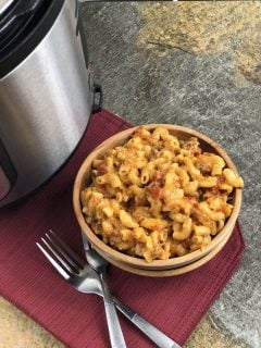 top view of cheesy goulash in a wooden bowl with 2 forks next to instant pot