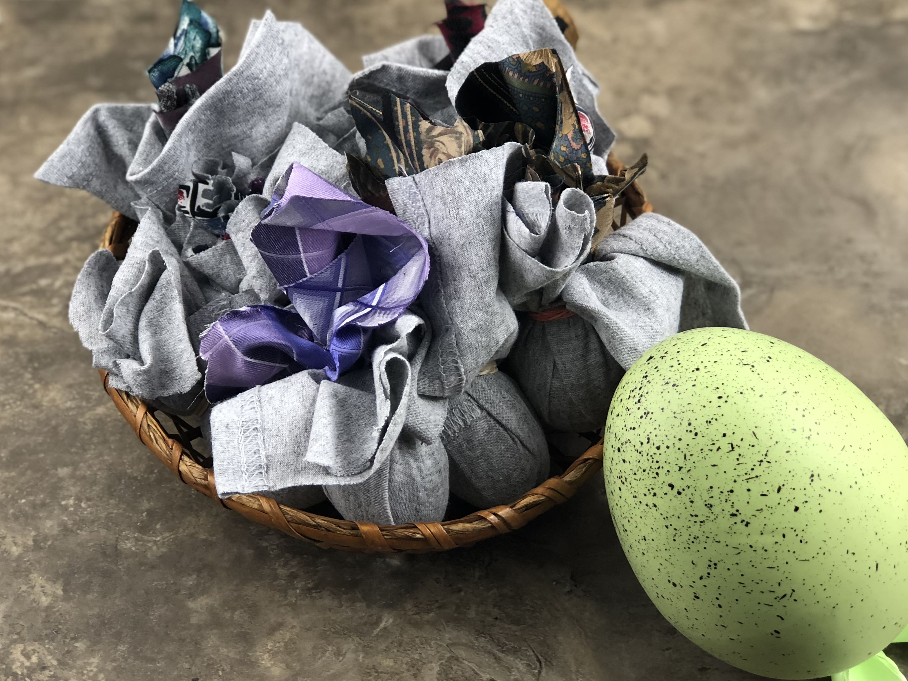 silk dyed eggs wrapped in ties in a basket