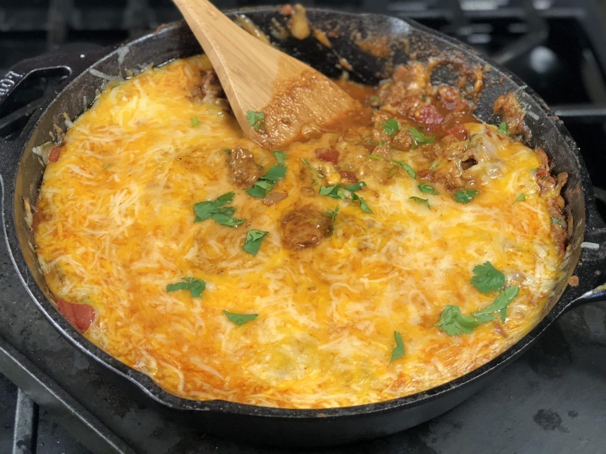 cheesy taco skillet with wooden spoon sticking out of a skillet