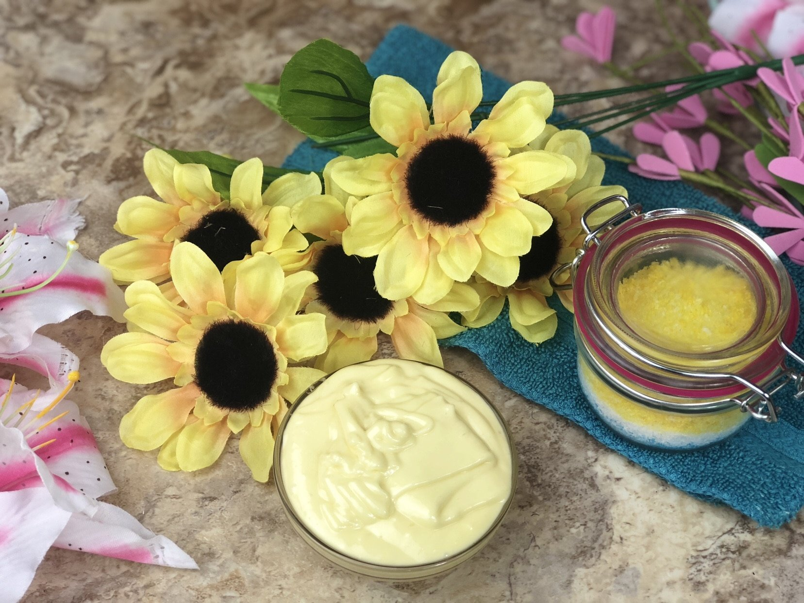 Curl Cream in a small bowl with yellowflowers and salt scrub on a blue towel.
