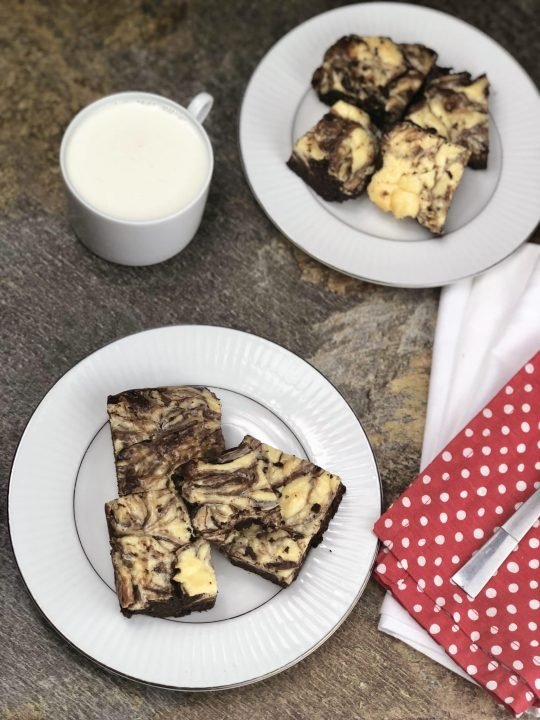 keto cheesecake swirl brownies on white plate with red napkin and mug of milk