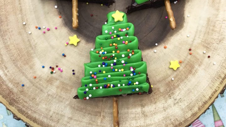 christmas tree brownies on a log, decorated with green icing, sprinkles and a star