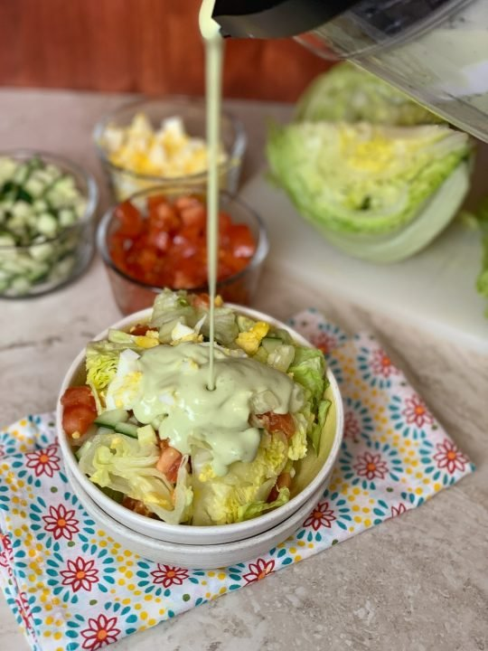 salad in white bowl sitting on top of a colorful napkin with salad fixings and lettuce in the back with avocado ranch dressing being poured on