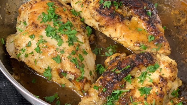 close up of 3 lemon pepper chicken breast in a skillet topped with parsley