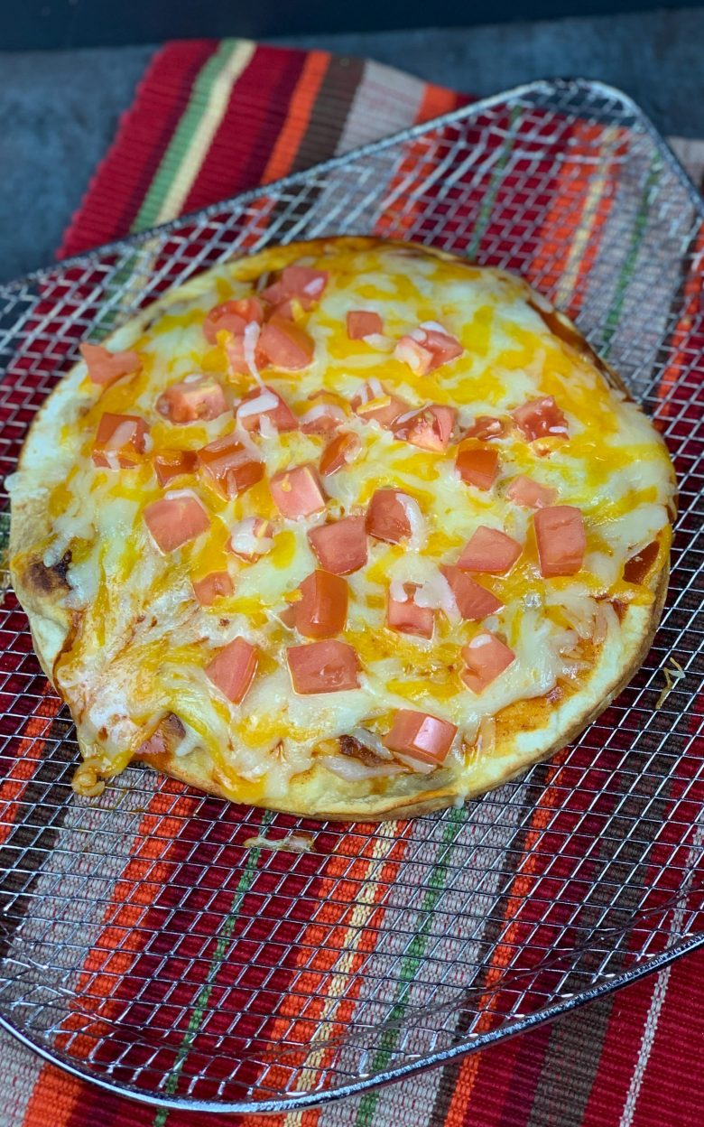 mexican pizza on a wire rack on top of a striped placemat