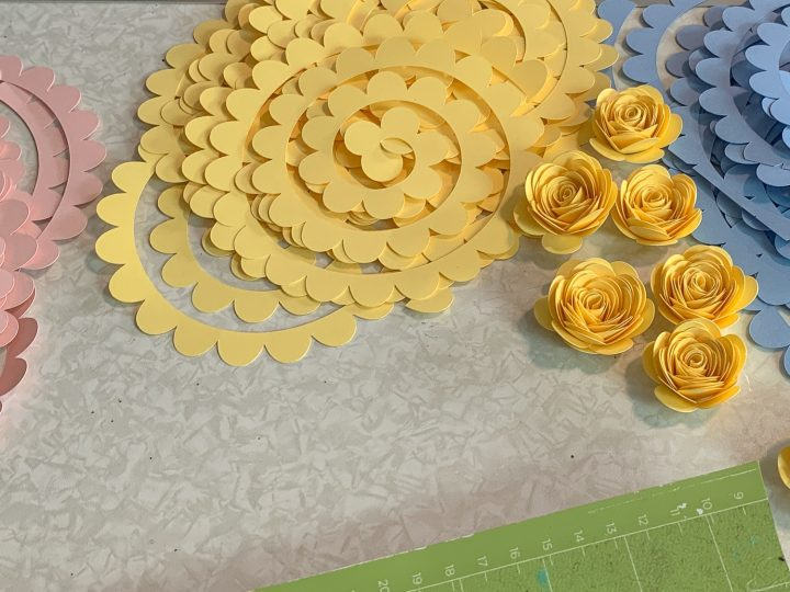 yellow flowers and paper cut outs for paper roses sitting on a table with blue and pink paper cut outs in back