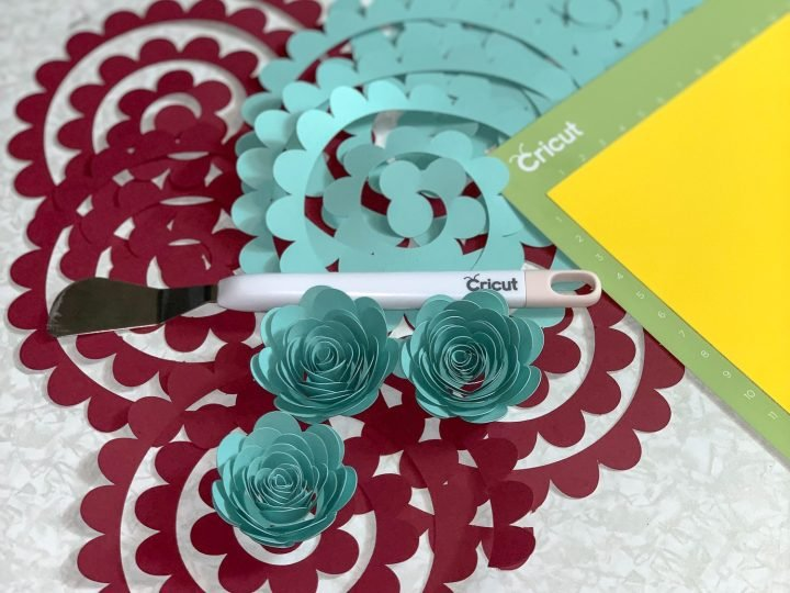 cricut spatula sitting on top of burgundy and teal paper cut out for paper flower