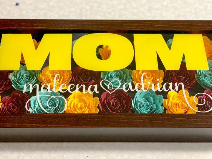 rolled flower shadow box made with yellow, teal and burgundy flowers with the words mom in yellow and 2 names in white