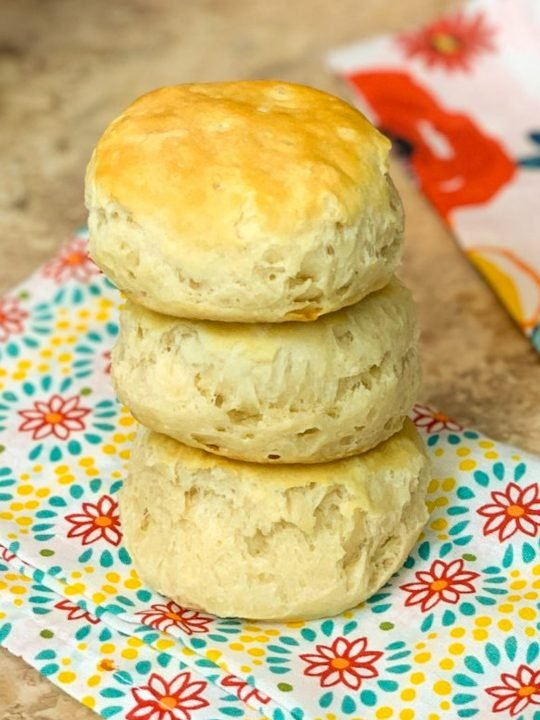 3 stacked homemade air fryer biscuits with a colored floral cloth napkin under them