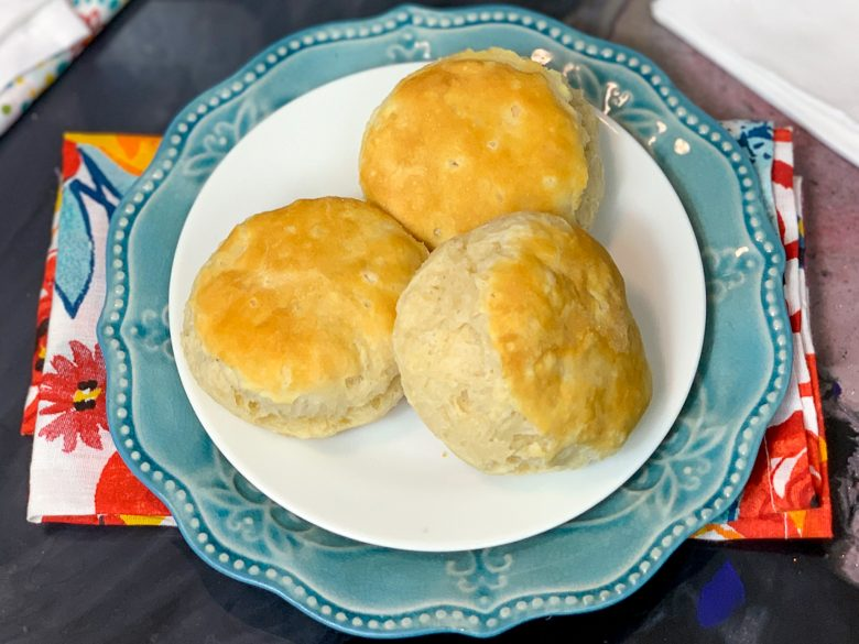 3 Air fryer biscuits on stacked plates with a floral cloth napkin underneath