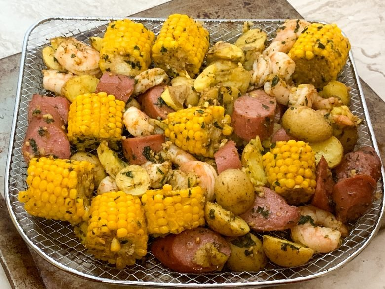 shrimp boil with corn, potatoes, shrimp, and sausage in a rack made from in an air fryer