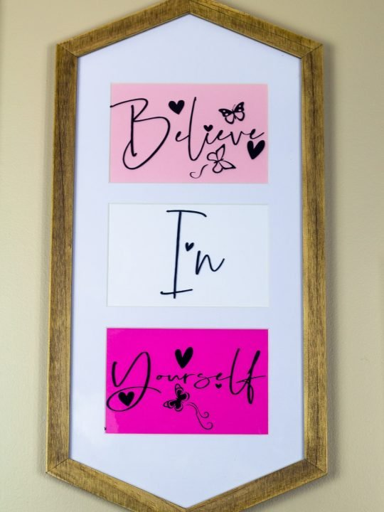 A framed sign with white background with believe in yourself in colorful arrangement for a Cricut DIY wall art project.