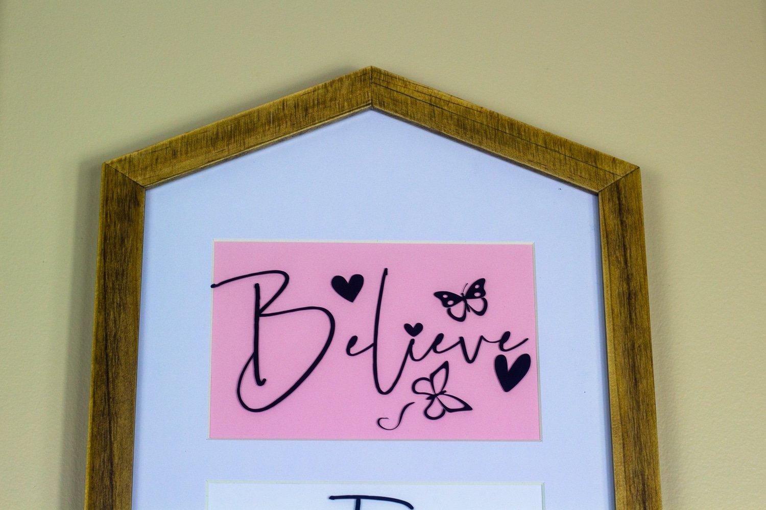 A framed sign with white background, pink graphic with the words believe on it.