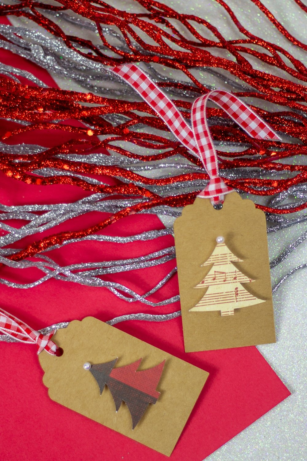 Image of a Christmas tree with note music gift tag with red and silver gilttery pip cleaners in the background.