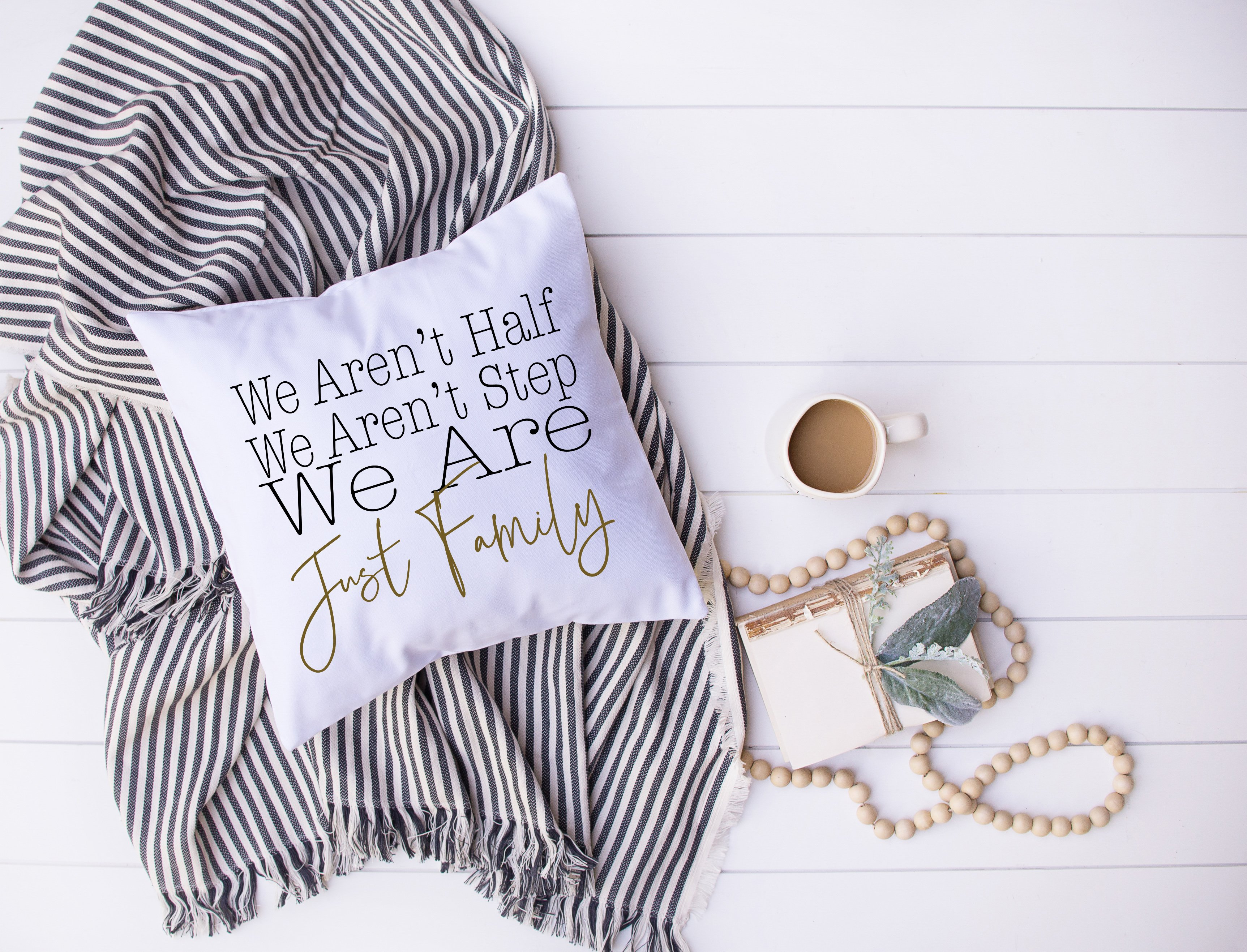 An image of a pillow that says We Are Just Family with black and white scarf in background and a necklace and coffee on the side.
