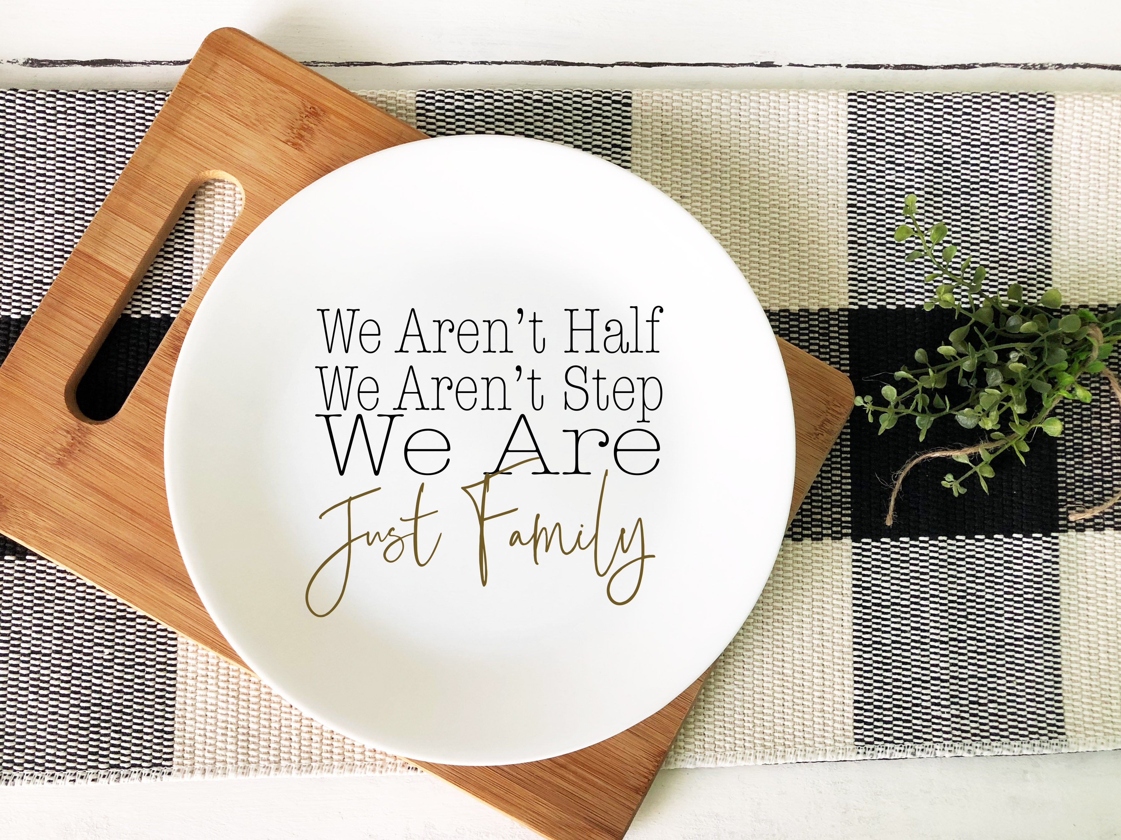 Image of a plate that says we aren't half, we aren't step, we are just family with a carving board and black and white checkered table cloth in background.