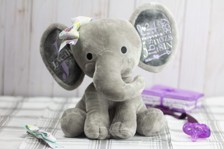 personalized stuffed animal with fabric bow and purple and white text on the ears