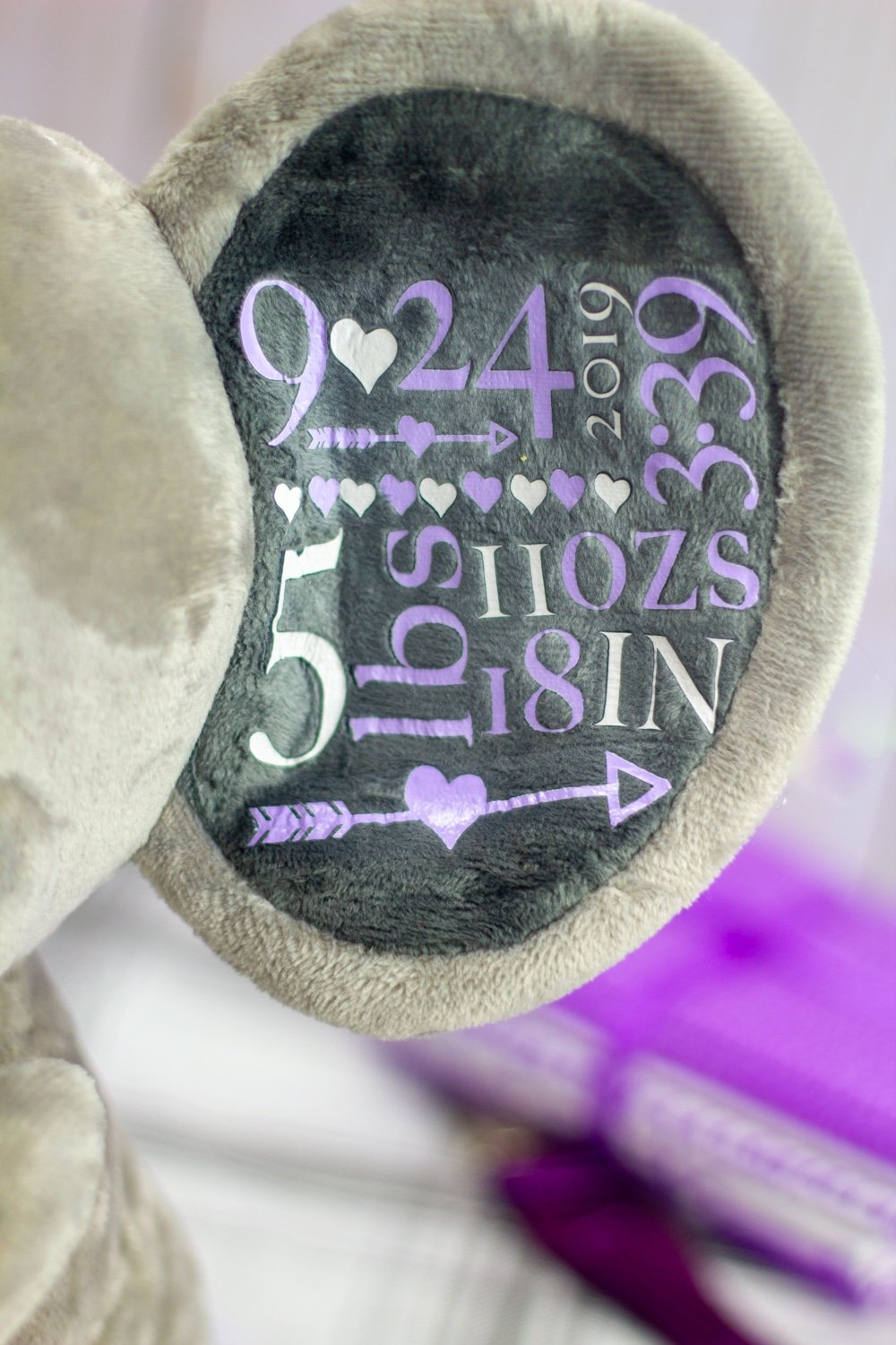 close up of purple and with white htv birth stats pressed onto a gray stuffed elephant with the easypress mini