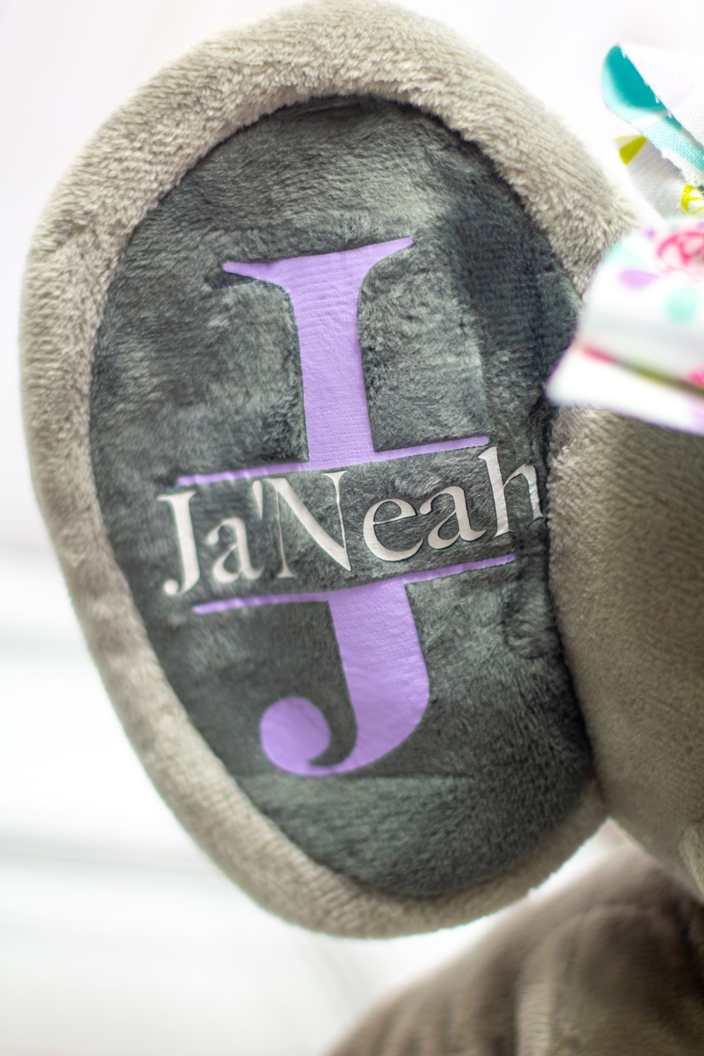 close up of purple initial with white name htv pressed onto a gray stuffed elephant with the easypress mini