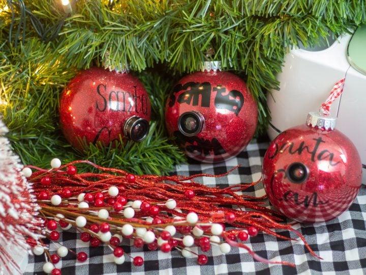 3 red santa cam ornaments sitting on a buffalo plaid cloth