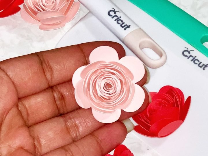 pink paper rose sitting in a hand with cricut supplies behind it made from a free rolled flower template template