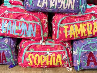 stacked duffle bags with vinyl lettering
