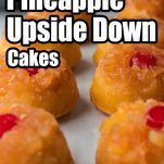 several mini cakes lined up on a baking sheet with pineapplea nd brown sugar topped with cherries with text which reads mini pineapple upside down cakes