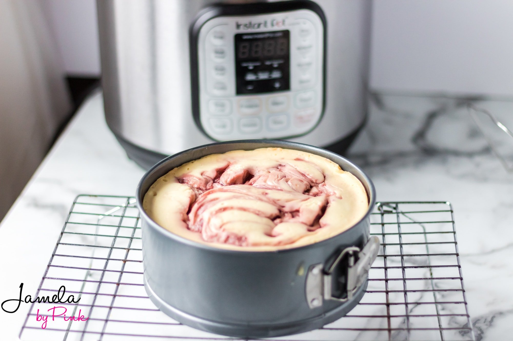 strawberry swirl instant pot cheesecake in a springform pan in front of an instant pot