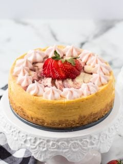whole strawberry cheesecake on a white cake plate