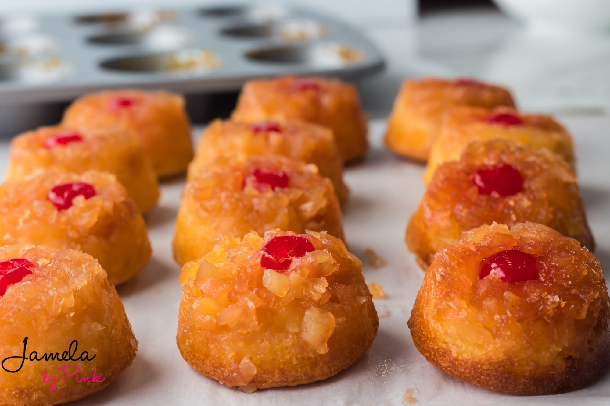 mini pineapple upside down cakes lined up on a white table