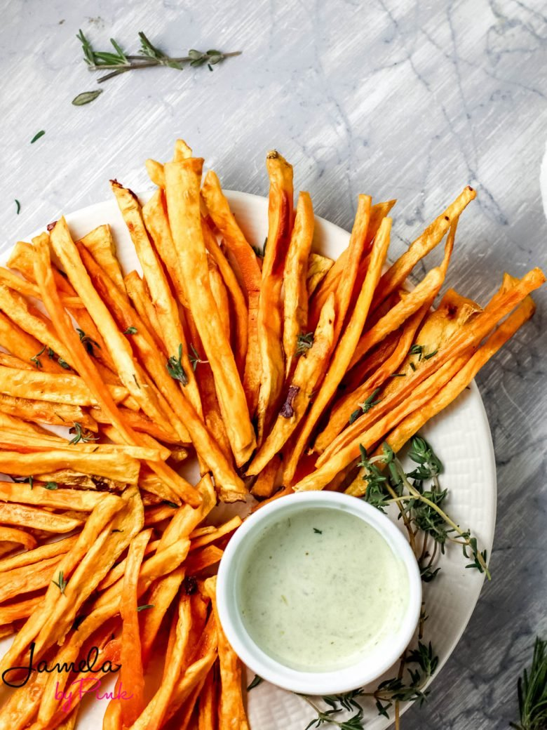 top bottom shot of sweet potato fries on a white plate with gray background with garlic herb dip on the side