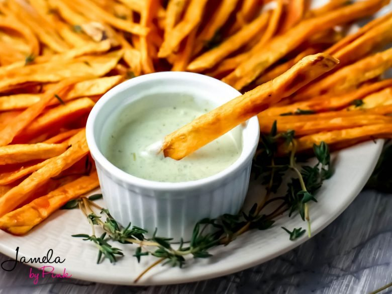 close up of sweet potato fries on a white plate with gray background with a fry in tje garlic herb dip on the side