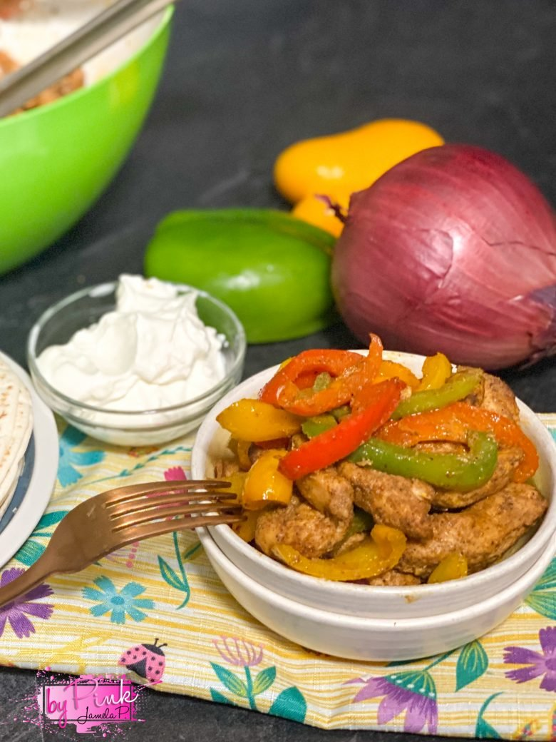 air fryer chicken fajitas in a white bowl with green, orange, yellow and red bell peppers on a floral napkin