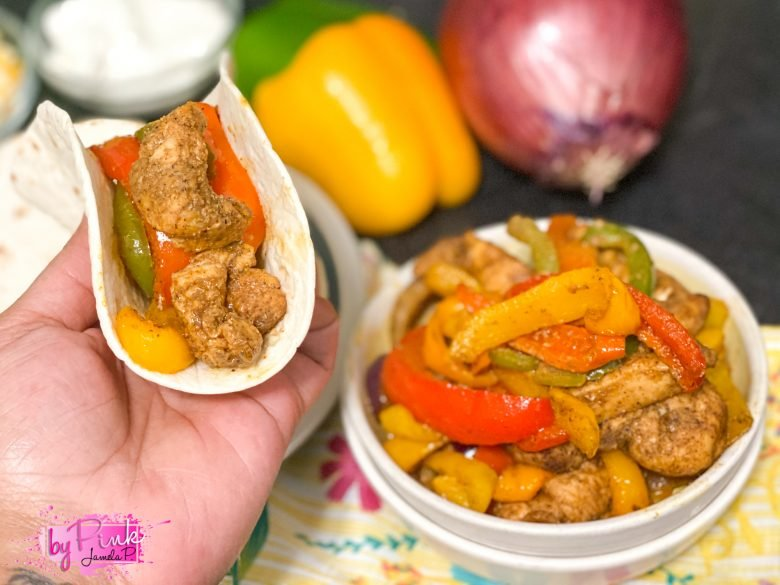 air fryer chicken fajitas in a white bowl with green, orange, yellow and red bell peppers with a hand holding a fajita wrapped in a flour tortilla