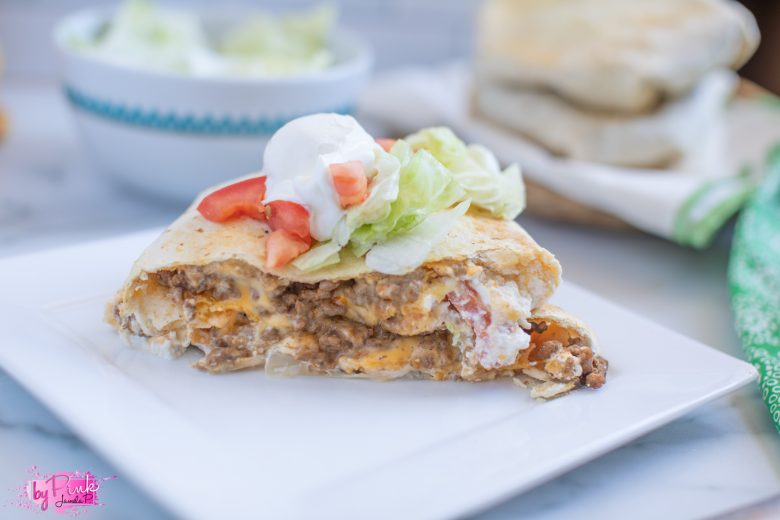 homemade taco bell crunchwrap supreme front view on a white background