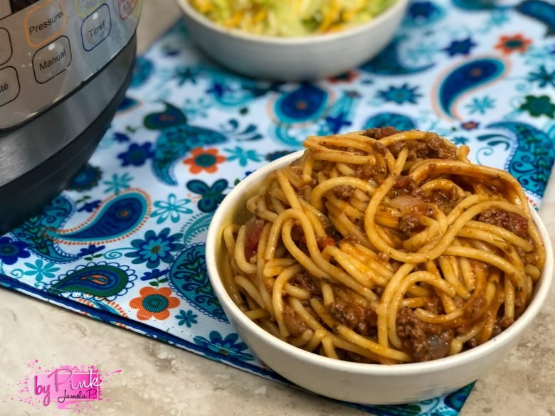 Top side view of the best instant pot spaghetti with an instant pot in the photo on a blue paisley placemat