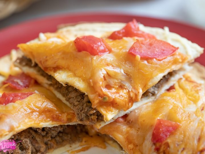 Image of taco bell Mexican pizza with melted cheese, tomatoes and refried beans and meat on a red plate with a blurry background.
