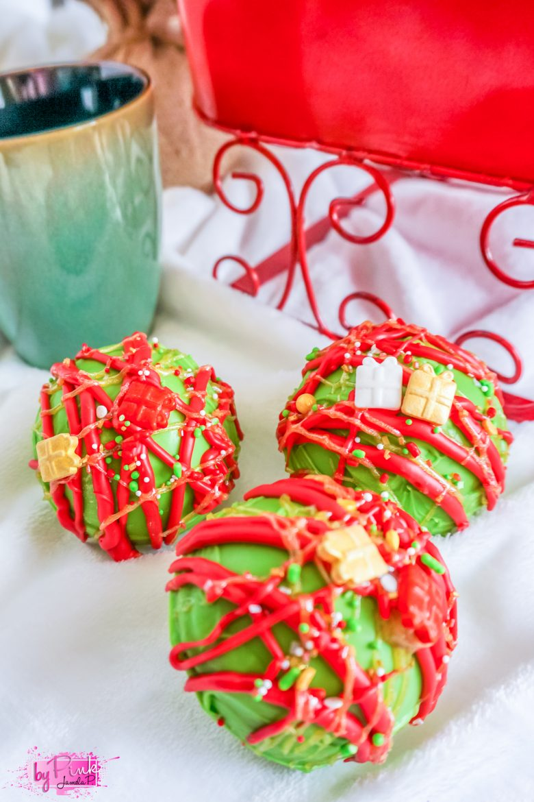 close up of red and green hot chocolate bombs with a sleigh in the background. green mold with red lines all over it