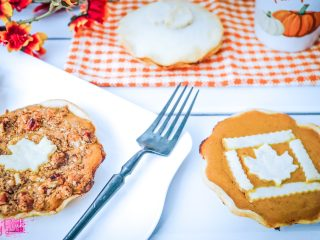pumpkin pies with fall leaf decor on top on orange and white plaid table napkin and plate