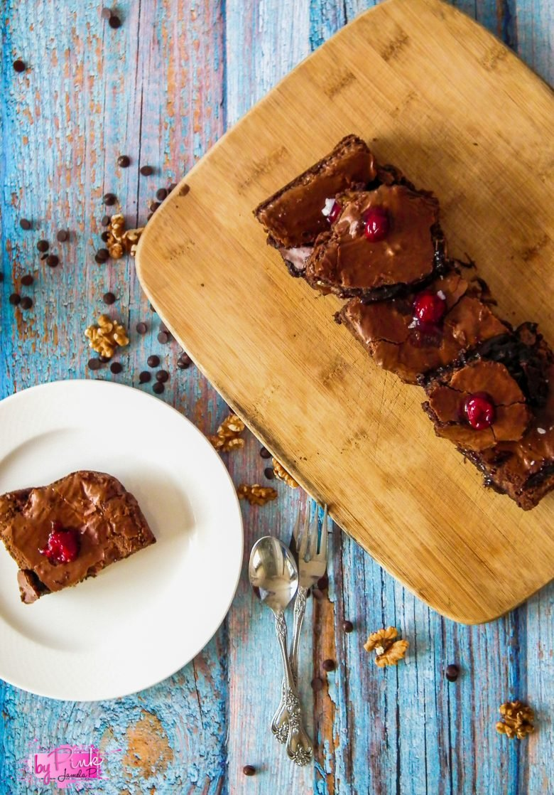 fuggy snacks with cherries on a wooden cutting board and a white plate on the side with one brownie