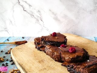 three walnut brownies with cherries on wooden cutting board from side angle
